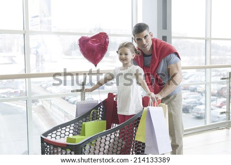 Father pushing young daughter in shopping trolley with shopping bags - stock photo