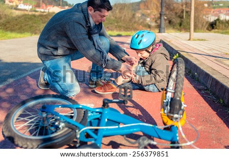 Father putting a plaster band over knee injury to his son after falling off to the bicycle - stock photo