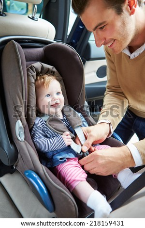 Father Putting Baby Into Car Seat - stock photo