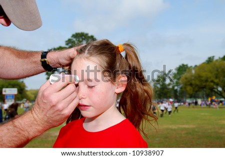 Father putting sunscreen on daughter's face at soccer field - stock photo