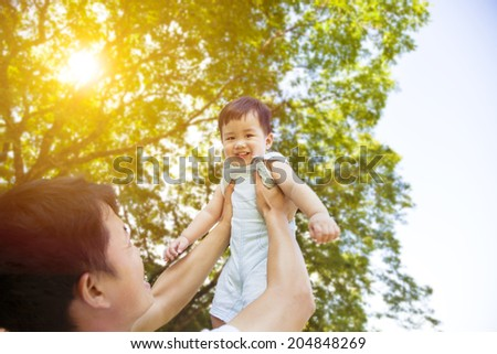 father raise high his cute son up with sunny background - stock photo