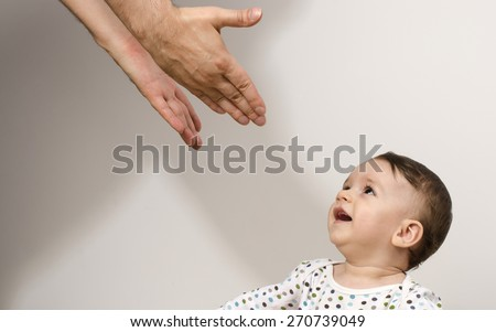 Father reaching to his beautiful baby. Newborn happy to see his father trying to protect and showing him love  - stock photo