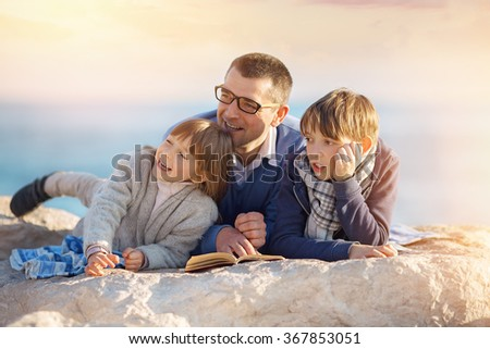 Father reading a book to his children outdoors - stock photo
