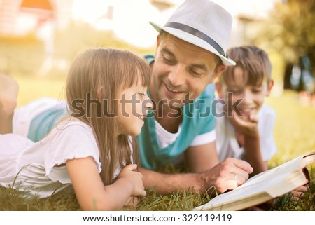 Father reading a book to his children while laying outdoor on the grass in the park