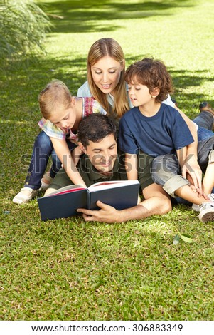Father reading book to family and his two children in a garden - stock photo