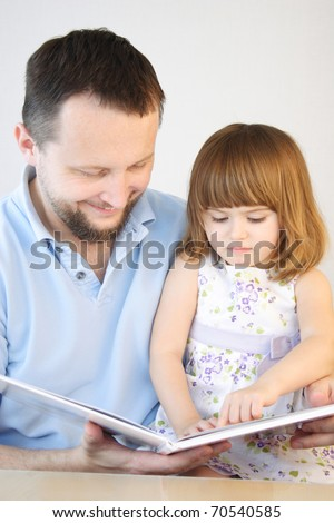 Father reading stories to his little daughter - stock photo
