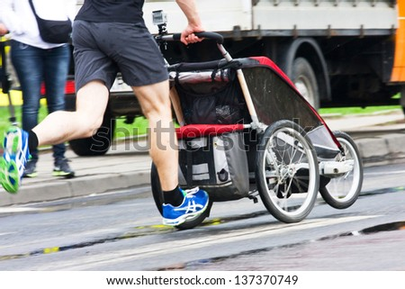 Father run with baby stroller in marathon - stock photo