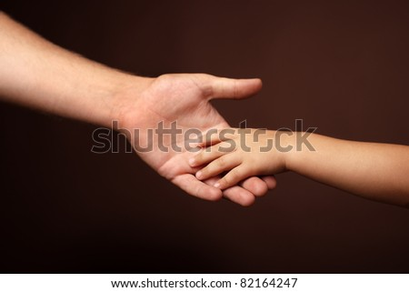father's and son's hands. soft focus - stock photo