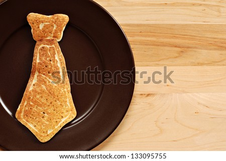 Father's day background image with real pancake in the shape of a necktie on plate.  Closeup with wood background and copy space. - stock photo