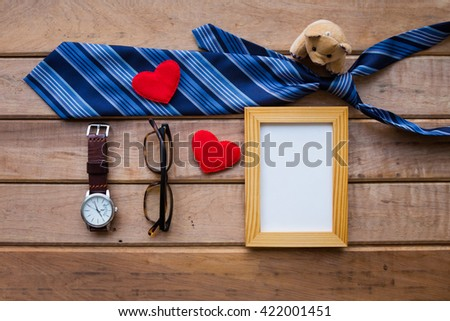 Father's day background with blue necktie, brown teddy bear, wooden photo frame, watch and glasses on rustic wooden background - stock photo