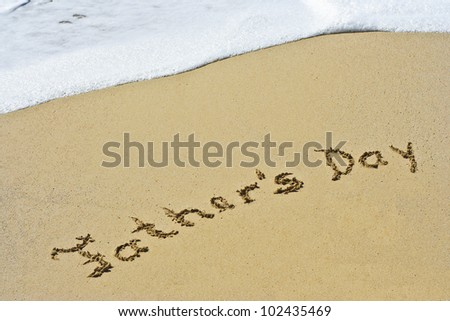 Father`s Day hand written in the sandy beach