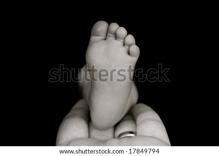 Father's hand holding his daughters foot