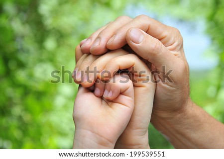father's hand holds a palm of his wife and daughter - stock photo
