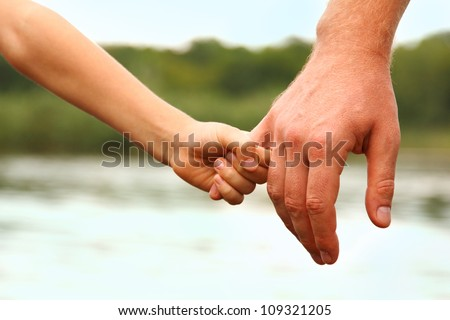 father's hand lead his child son against summer forest and river nature outdoor background, trust family concept - stock photo