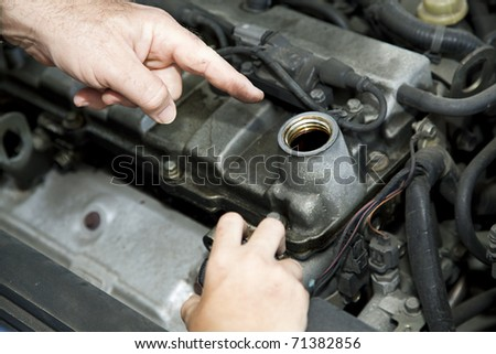Father's hand pointing to the oil reservoir in the automobile engine.  Son's smaller hand holding the oil cap. - stock photo