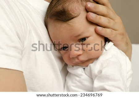 Father's hands holding his newborn with love, protecting him, innocent baby feeling safe at his father chest - stock photo