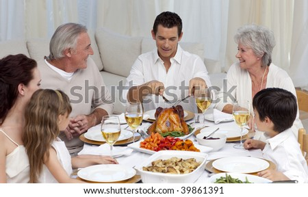 Father serving turkey to his family in a dinner at home - stock photo