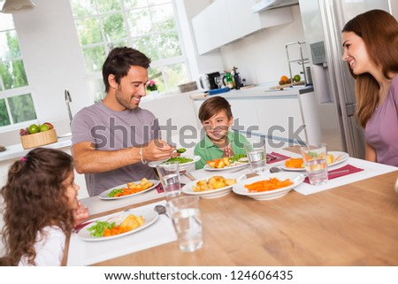Father serving vegetables to son in kitchen - stock photo
