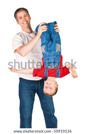 Father shaking his son upside-down on white background - stock photo