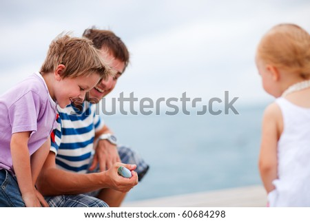 Father showing caught fish to his son and daughter. Focus on fish. - stock photo