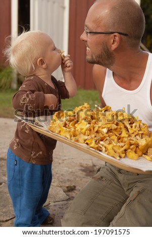 Father showing chanterelle to his son - stock photo
