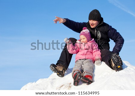 Father showing his daughter aside. Family in winter - stock photo