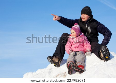 Father showing his daughter aside. Family in winter