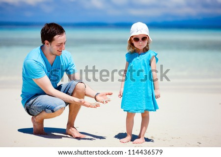 Father showing his little daughter two starfish