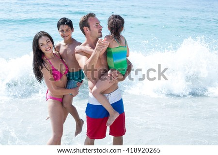 Father showing to daughter while mother standing besides with son at beach - stock photo