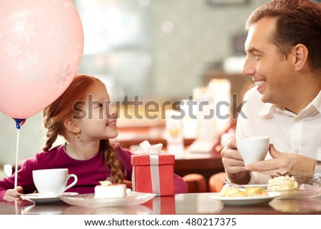 Father sitting in cafe with his little girl at her birthday