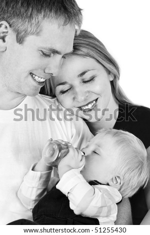Father sitting on the armchair with his baby drinking milk and wife near him - stock photo