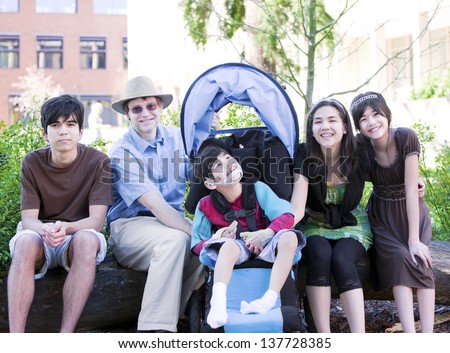 Father sitting with his biracial children and disabled son in wheelchair. Child has cerebral  palsy. - stock photo