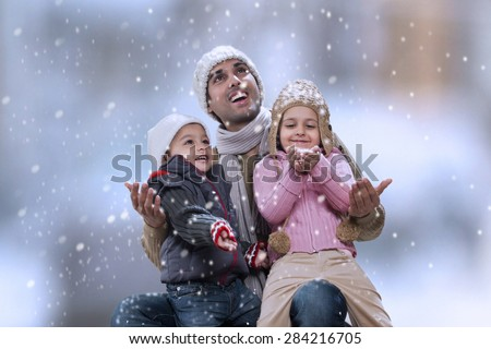 Father sitting with kids as it snows - stock photo