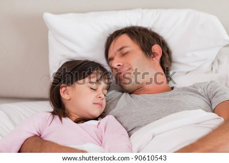 Father sleeping with his daughter in a bedroom - stock photo