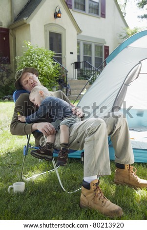 Father sleeping with son in his lap while camping in the front yard - stock photo
