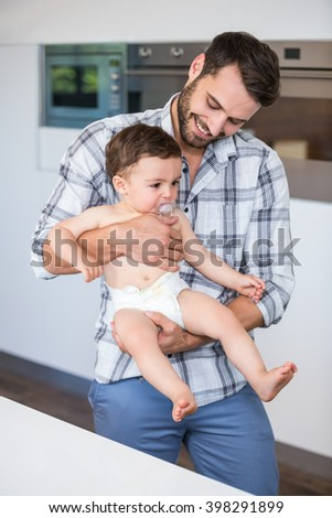 Father smiling while carrying son by table at home - stock photo