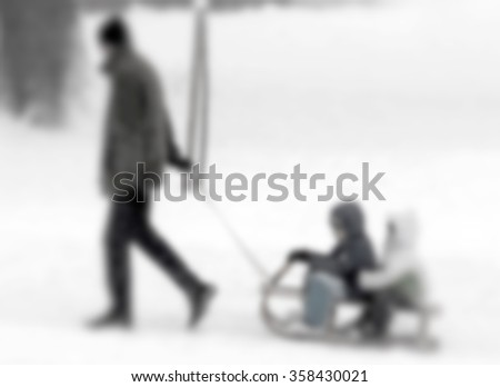 Father son and daughter on the snow-blurred - stock photo