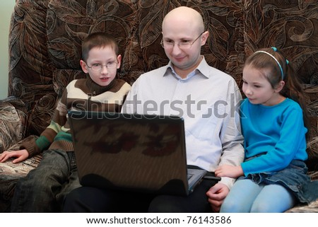 Father, son and daughter sitting on couch and look at laptop screen - stock photo