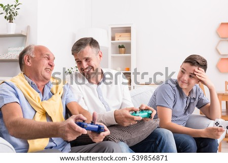 Father, son and grandson playing video games
