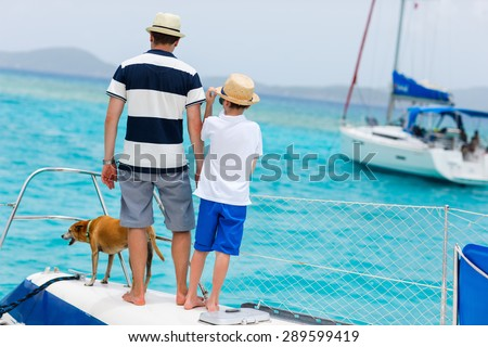 Father, son and their pet dog sailing on a luxury yacht or catamaran boat - stock photo