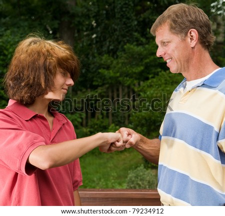 Father-son fist bump: funky long-haired teen boy and traditional-looking dad - stock photo