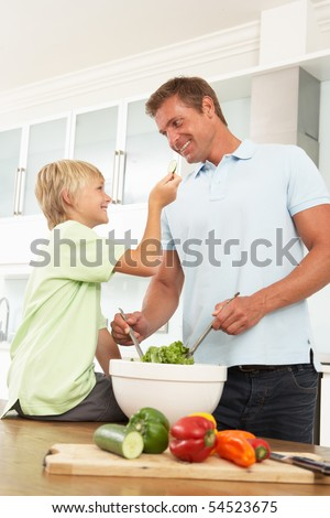 Father & Son Preparing Salad In Modern Kitchen