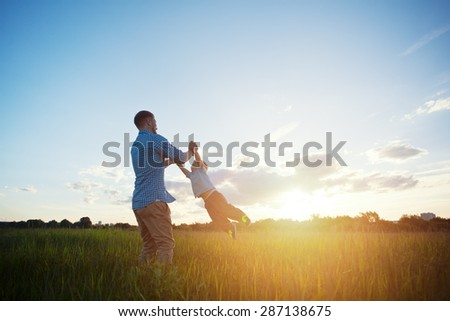 father spinning with his son in the park at sunset (intentional sun glare) - stock photo