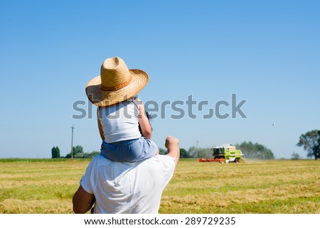 Father standing on field riding son on shoulders pointing at harvester -thresher on summer sunny day over blue sky background copyspace - stock photo
