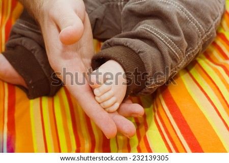 Father stroking your baby's foot - stock photo