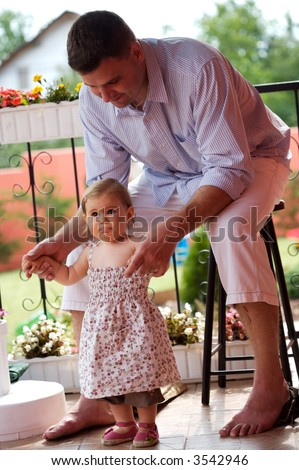 Father supports his baby girl in her first steps  at home, outdoor in the garden.