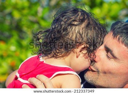 Father sweet kiss to his daughter. - stock photo