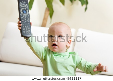 Father switch on a TV, please! Cute little boy at home reach remote control to parent and want to watch TV. - stock photo