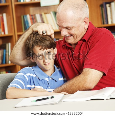 Father takes a break from helping his son with homework to give him noogies. - stock photo