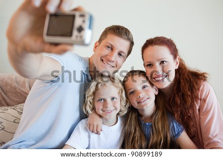 Father taking a family picture on the sofa - stock photo